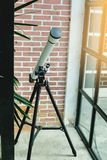 White telescope with brick wall royalty free stock images
