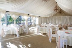The white tent is decorated with textiles and candlesticks on the wedding day. Solemn action royalty free stock photo