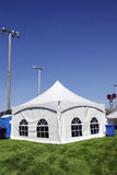 White tent on grass vertical. Celebration or event: White tent on soccer field with lighting ready for guests in case of rain with sound system on lift in the Stock Images
