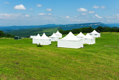 White tent on the green grass in the mountains Stock Photography