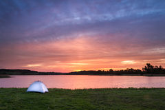 White tent and rising sun on the lake Stock Photos
