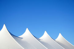 White Tent Tops. White canvas event tents against blue sky Stock Photo