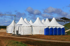 White tents at the exhibition camp. White awnings and other items of equipment for arrangement of exhibition stock photo