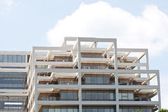 White Terraced Office Tower Under Sunny Skies. A white office tower with balconies and terraces under a bright sunny sky stock photos