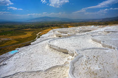White terraces of Pamukkale against multicolored landscape Stock Photo
