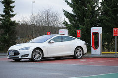 White Tesla Model S being Charged at Supercharger Station Stock Image