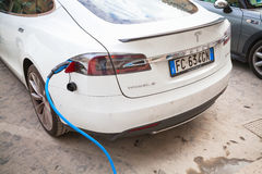 White Tesla model S car charging at recharging station. Rome, Italy - February 13, 2016 : White Tesla model S car charging at the EV public recharging station in Royalty Free Stock Image