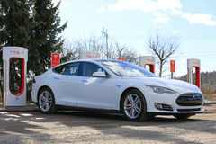 White Tesla Model S at Supercharger stock photography