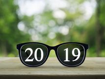 Business vision, Happy new year 2019 concept. 2019 white text with black eye glasses on wooden table over blur green tree in park, Business vision, Happy new royalty free stock photography