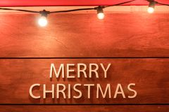 White text merry christmas on wooden background.  Royalty Free Stock Photography
