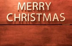 White text merry christmas on wooden background.  Stock Photos