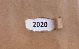 2020 white text under brown old torn paper. Shipping delivery. 2020 white text under brown old torn paper, panorama, copy space stock images
