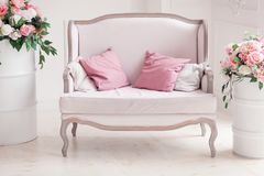 White textile classical style sofa with pillows. Flowers ob painted barrels. Close-up shot.  Royalty Free Stock Image