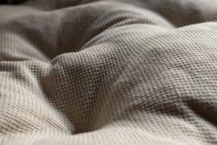 White textile pillow. Wavy textile surface stock photo