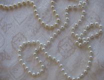 White textured background of lustrous pearls on a rich patterned fabric stock photo