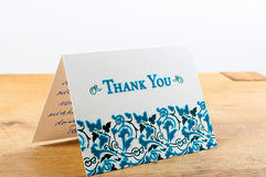 White thank you card with blue letters with note written by hand Stock Photos