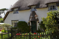 White thatched country cottage. With flower filled garden Stock Photo