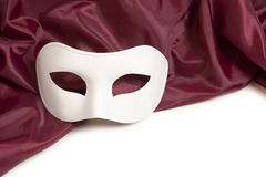 White theatrical mask. And red silk fabric on a white background Royalty Free Stock Photos