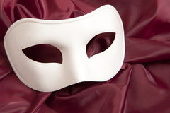 White theatrical mask. And silk fabric royalty free stock photography