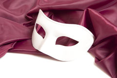 White theatrical mask and silk fabric Stock Photos