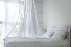 White themed bed sheets and white curtain in the morning, bedroom interior. Hotel or home Stock Photo