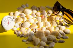 White thermometer with a temperature of +26 degrees Celsius, sunglasses and a lot of different seashells on a yellow background. The concept of hot summer stock image