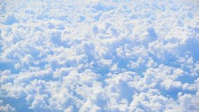 White thick fluffy clouds accumulation under moving plane, adventurous soul