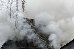 White smoke comes from the burning roof of the house. White thick smoke comes from the burning roof of the house stock photo