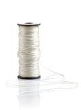 White thread on reel. On white background Royalty Free Stock Photo