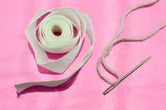 White thread, ribbon and needle Stock Photos