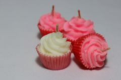 White and three pink candles in cupcake shape put on light grey background. Royalty Free Stock Photos