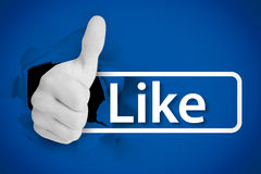 White thumb up tearing a canvas with the like from social networks royalty free stock photo