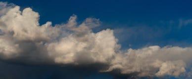 White thunderous cumulus clouds on dark blue summer sky, panoramic photo. Royalty Free Stock Photo
