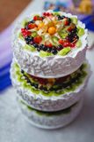 White tiered cake with chunks of berries and fruits Royalty Free Stock Photography