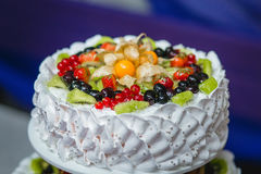 White tiered cake with chunks of berries and fruits Stock Photo