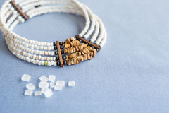 White and tiger stone beads necklace on a blue background with refined sugar Stock Images