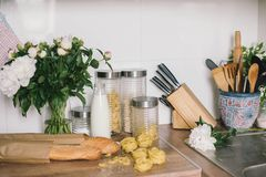 White tiles wall modern kitchen with chopping board,flowers,knifes,pasta,bread. White tiles wall modern kitchen with white top background and ingredients royalty free stock image