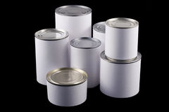 White tin cans on black background. Seven tin cans of different sizes with white labels Royalty Free Stock Photo