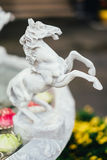 White tiny horse statue with yellow flower in the background Royalty Free Stock Images