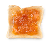 White toast topped with peach jam. Overhead view of a slice of white toast topped with vibrant orange apricot or peach jam royalty free stock images