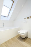 Stylish attic bathroom in white. White toilet, bathtub and wooden floor in stylish attic bathroom Royalty Free Stock Images