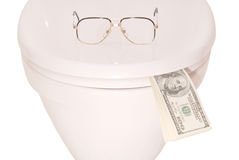 White toilet bowl glasses and money (Clipping path). Points on the lid of the toilet and money isolated with path Royalty Free Stock Photo
