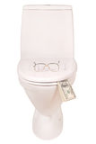 White toilet bowl glasses and money (Clipping path). Points on the lid of the toilet and money isolated with path Royalty Free Stock Photography