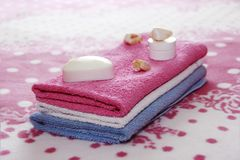 White toilet soap and decor against the background of pink terry towels stock photo