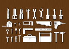 White tool kits. And black stroke on brown wood texture background Stock Image