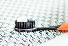 White toothpaste on black toothbrush Royalty Free Stock Photo