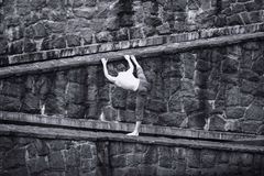 White topless man stretching at stony wall Royalty Free Stock Photo