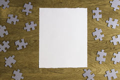 White torn paper piece surrounded by puzzle pieces on wooden background. Top view. Copy space for text Stock Photo