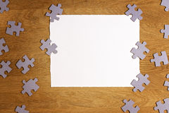 White torn paper piece surrounded by puzzle pieces on wooden background. Top view. Copy space for text Royalty Free Stock Photo