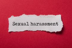 White torn paper on red paper background with text - Sexual harassment. Closeup of white torn paper on red paper background with text - Sexual harassment royalty free stock photos